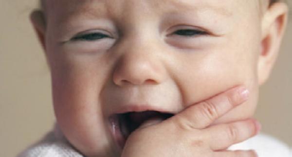 Bebé com dor e desconforto devido à erupção dentária